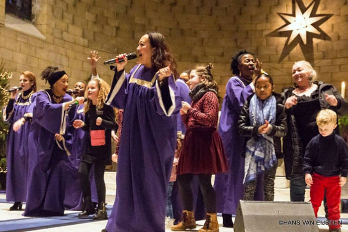 ABC Gospel Choir dressed in purple robes singing with the public at Maastricht Gospel Festival